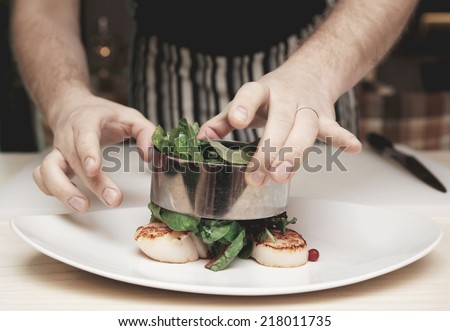 Chef is cooking appetizer with sea scallops and salad mix, toned image - stock photo