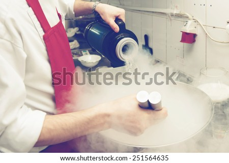 Chef is cooking ice cream with liquid nitrogen, toned image - stock photo