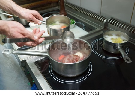 Chef is cooking ox tail, professional kitchen - stock photo