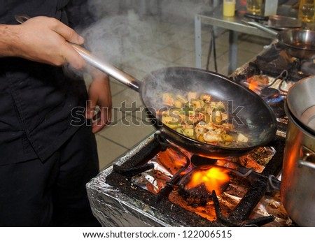 Chef is cooking seafood dish - stir fry method - stock photo