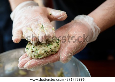 Chef is cooking zucchini fritters, motion blur - stock photo
