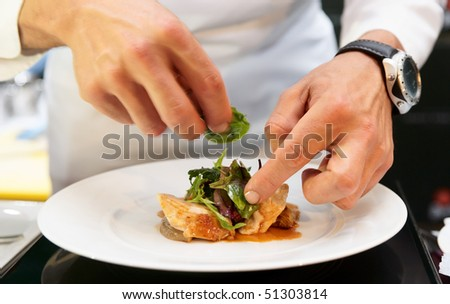 Chef is decorating delicious dish, motion blur on hands - stock photo