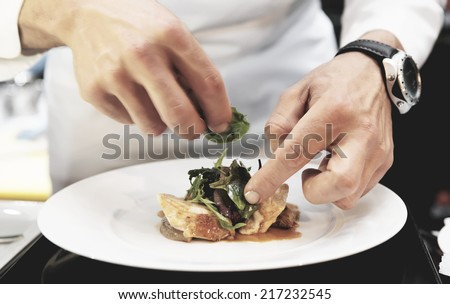 Chef is decorating delicious dish, motion blur on hands, toned image - stock photo