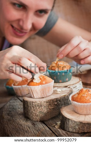 Chef is decorating delicious organic muffins. Almond and cherry cup cakes in natural setting. - stock photo