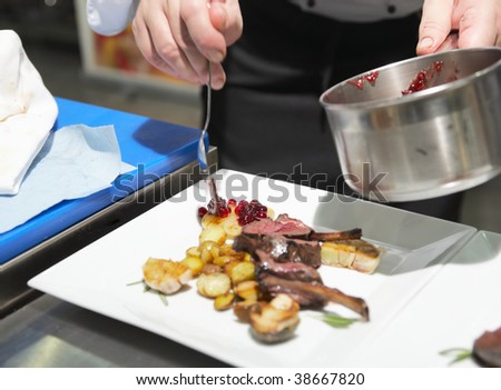 Chef is decorating grilled rack of lamb with currant sauce - stock photo