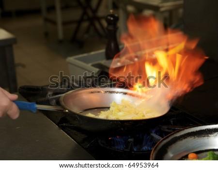 Chef is making flambe sauce on restaurant kitchen - stock photo