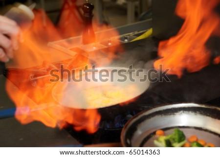 Chef is making flambe sauce on restaurant kitchen, motion blur - stock photo