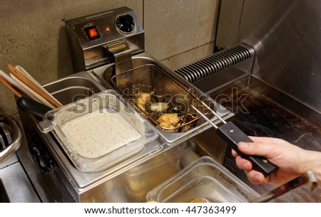 Chef is making nuggets, cheap fast food restaurant - stock photo