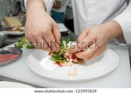 Chef is making tuna carpaccio in a restaurant - stock photo