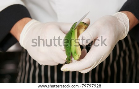 Chef is peeling avocado - stock photo