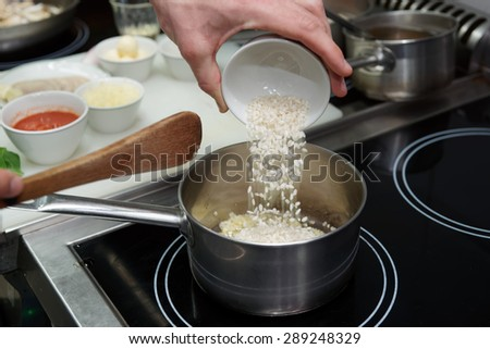 Chef is pouring rice in stewpan to cook risotto - stock photo