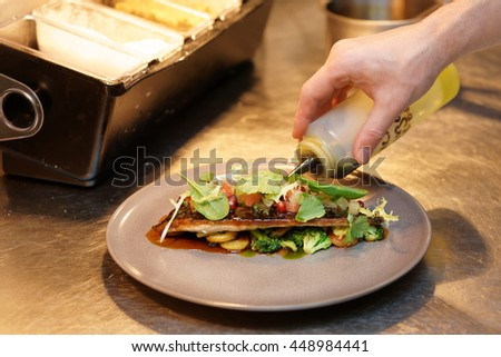 Chef is seasoning an appetizer with green aromatic oil - stock photo