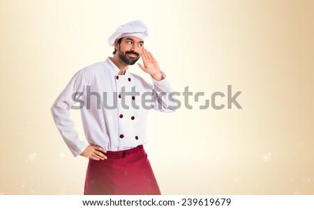 Chef listening over ocher background - stock photo