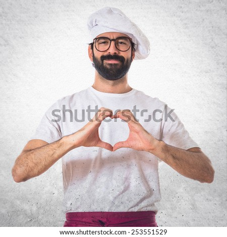 Chef making a heart with her hands - stock photo