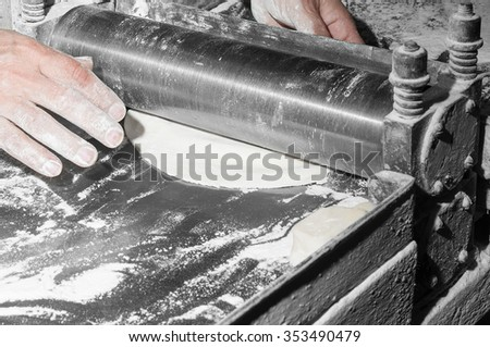 Chef making dough for pastry on dough sheeter, close-up - stock photo