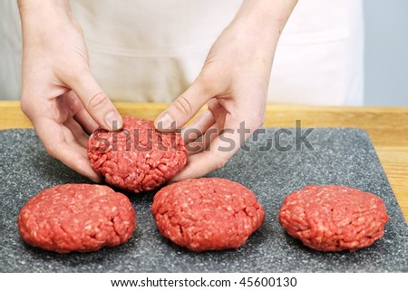 Chef making hamburger patties in kitchen with ground beef - stock photo