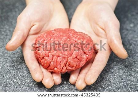 Chef making hamburger patty in kitchen with ground beef - stock photo