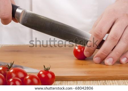 Chef Man cut vegetables on kitchen blackboard. - stock photo