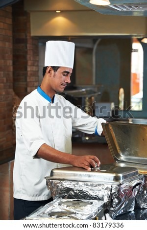 chef man in uniform boiling a soup on cooker in kitchen