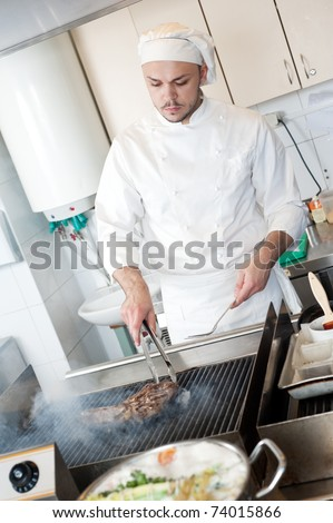 chef man in uniform frying a meat beefsteak slice on grill in kitchen - stock photo