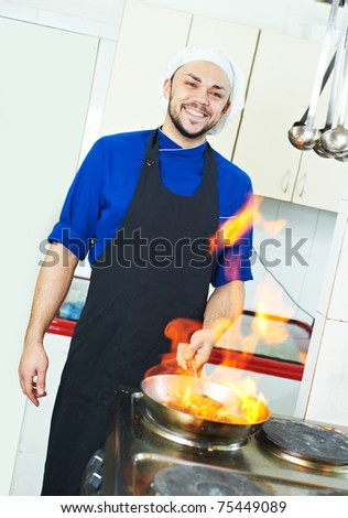 chef man in uniform making flambe meal with frying pan in kitchen - stock photo