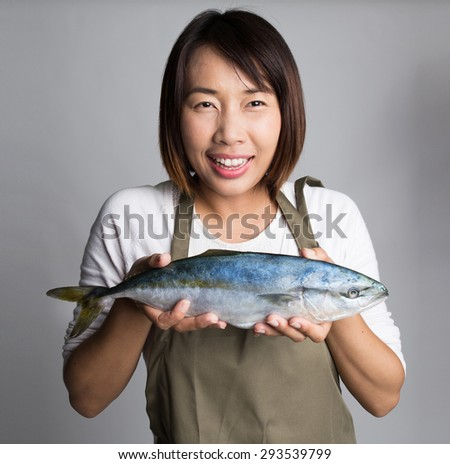 Chef or a female cooker or a housewife holding a big fresh raw fish, presenting, selling, or prepared. - stock photo
