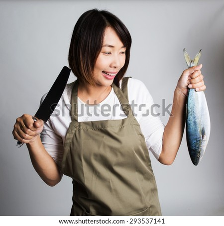 Chef or female housewife holding a big fresh raw fish and a knife - stock photo
