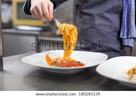 Chef plating up seafood pasta placing spaghetti twirled around a fork alongside a grilled prawn on a plate in a commercial restaurant - stock photo