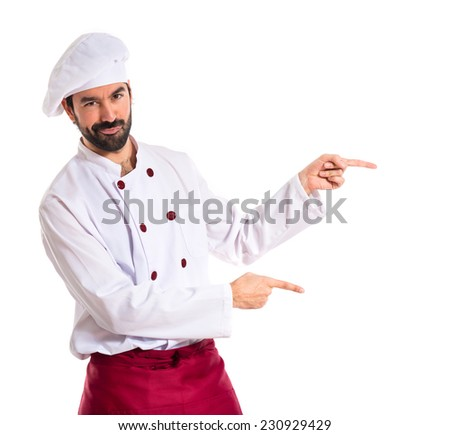 Chef pointing to the lateral over white background - stock photo
