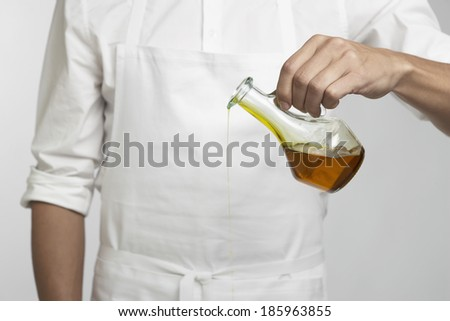 Chef pouring olive oil (mid section)