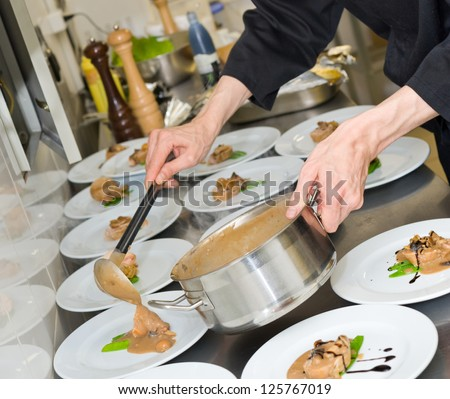 chef pours sauce over meat pieces on plates - stock photo