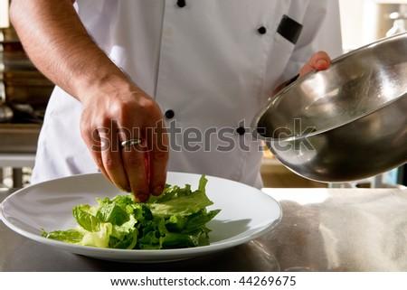 Chef prepare lettuce garnish for salmon steak - stock photo