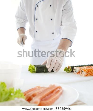 chef prepares Japanese food - sushi. On the table, the ingredients for sushi