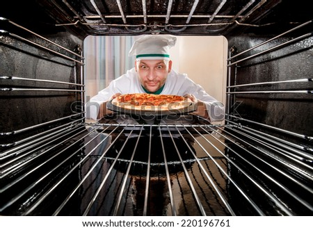 Chef prepares pizza in the oven, view from the inside of the oven. Cooking in the oven. - stock photo