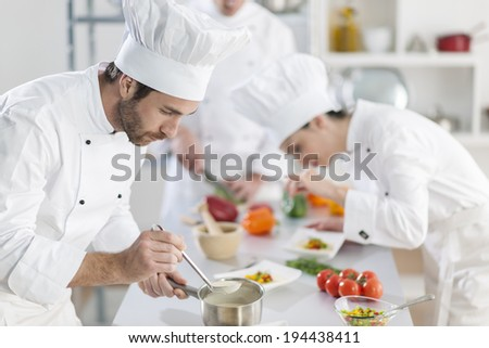 chef preparing a dish his team in the background - stock photo