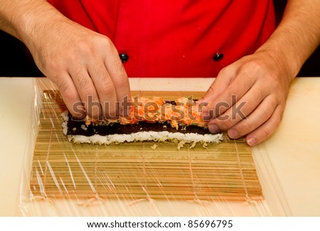 Chef preparing a roll of salmon sushi - stock photo