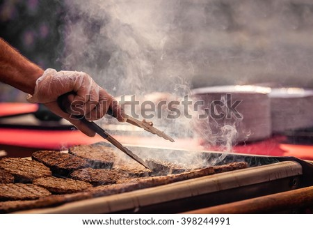 Chef  preparing burgers at the barbecue outdoors - stock photo