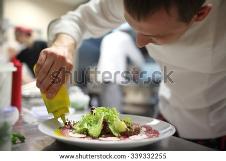 Chef preparing food  in kitchen - stock photo