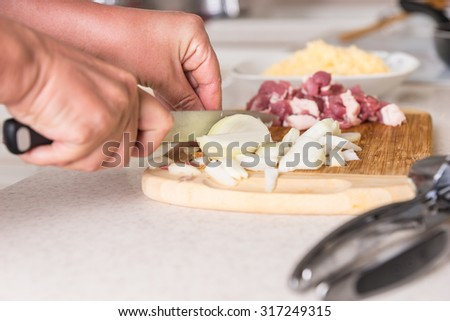 Chef preparing fresh ingredients for a meal chopping raw meat and fresh onions on a wooden chopping board in a kitchen, close up of his hands - stock photo