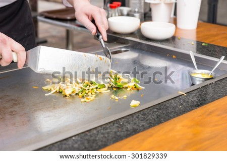 Chef preparing fresh vegetable stir fry on a large commercial hotplate or griddle at a restaurant, close up of his hands - stock photo