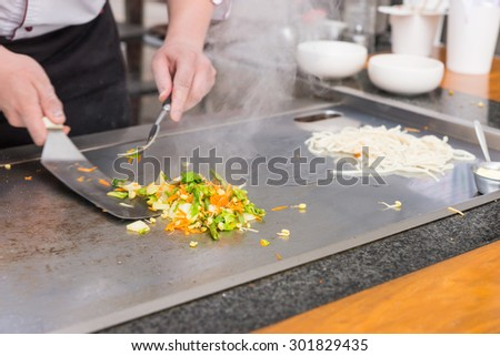 Chef preparing fresh vegetable stir fry over a hot plate turning it with a spatula as he cooks Asian cuisine at a restaurant, close up of his hands - stock photo