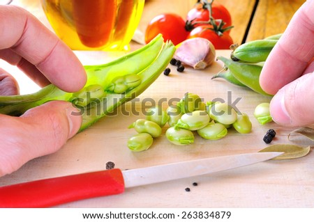Chef preparing some beans on a cutting board on a kitchen table - stock photo