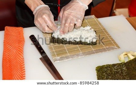 chef preparing sushi in the kitchen - stock photo