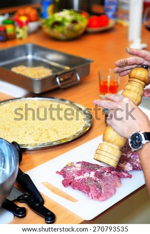 Chef preparing the meat and adds spices - stock photo