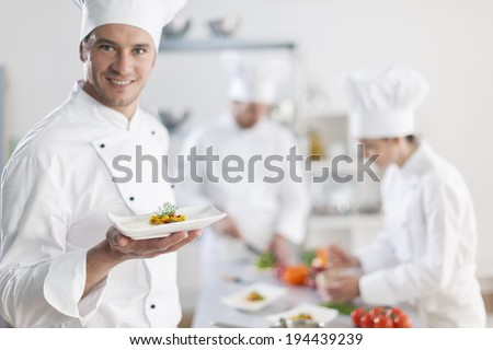 chef presenting a dish with his team in background - stock photo