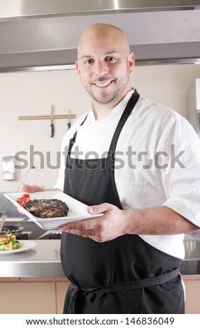 Chef presenting a juicy steak in the kitchen