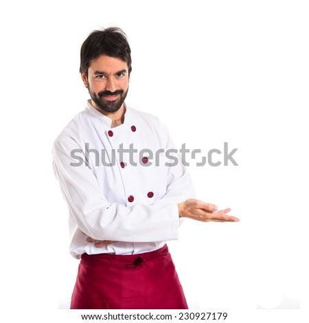 Chef presenting something over white background - stock photo