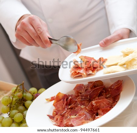 Chef puts jamon on a plate. Serrano, jamon. - stock photo