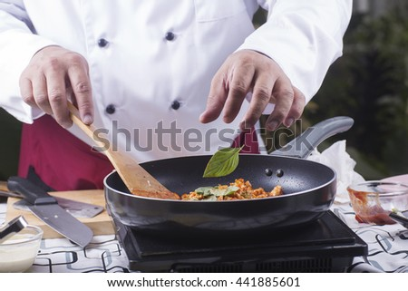 Chef putting basil to pan for cooking spaghetti chicken sauce / cooking spaghetti concept - stock photo