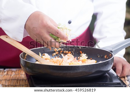 Chef putting bean sprouts and leek to the pan / cooking Pad Thai concept